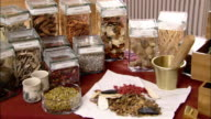Medium shot jars of herbs, mortar and pestle and various colored herbs laid out on table / pan to drawers of herbs