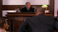 Medium shot judge requesting lawyers approach bench / judge talking to opposing lawyers