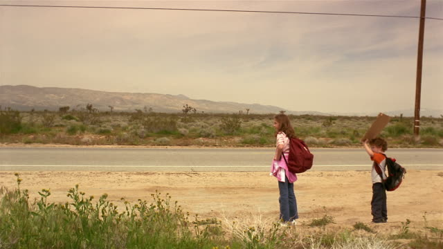 Medium shot kids holding up sign / car stopping / older couple driving away as parents run to car