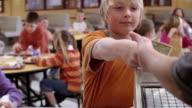 Medium shot kids pay for food in school cafeteria/ Goram, Maine