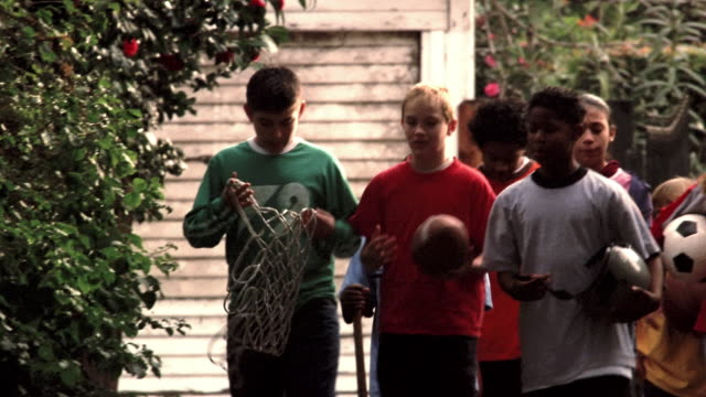 Medium shot kids talking and walking down driveway holding sports equipment / breaking into a run