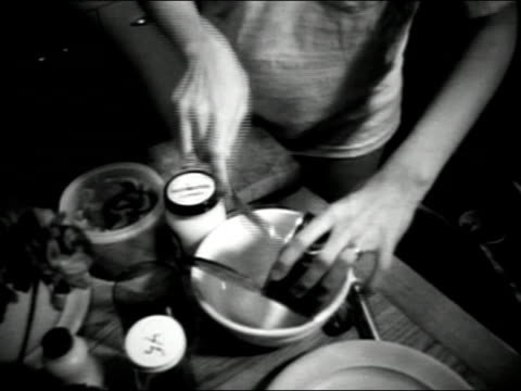 1971 Medium shot kitchen table as woman prepares meal