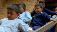 Medium shot large group of small schoolchildren descending steep stairs from school / Nepal