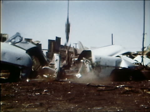 1961 medium shot large weight falling on car in junk yard and crushing it