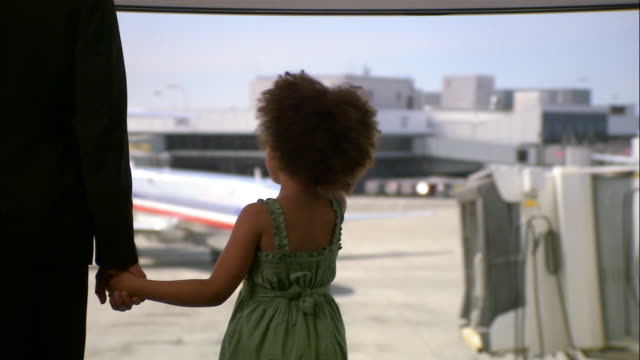 Medium shot little girl holding hands with adult while looking out window at airport gate/ Seattle