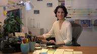 Medium shot lockdown businesswoman sitting at desk, looking at camera, smiling