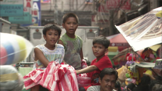 Medium Shot Locked Down - Boys sit on vehicle and smile at the camera on teeming market street / Manila Philippines