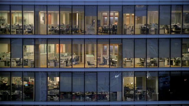 Medium shot looking into glass office building at night / London