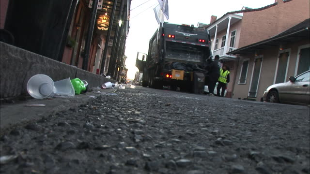 Medium Shot Low Angle - Men dumping trash into garbage truck / New Orleans Louisiana