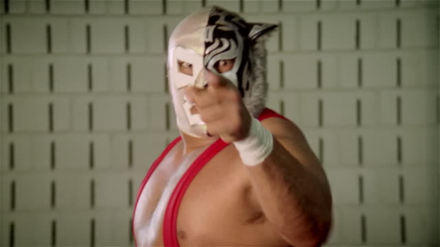Medium shot luchador 'Black Tiger' flexing muscles, sticking tongue out, and pointing at camera/ close up mask/ Monterrey, Mexico