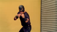 Medium shot luchador 'Shadow' turning to face camera in wrestling stance/ turning to profile/ turning to camera/ zoom in mask/ Monterrey, Mexico