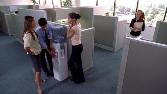 Medium shot male and female workers talking by water cooler in office w/cubicles