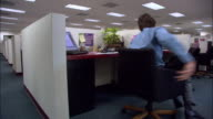 Medium shot male office worker sitting and spinning in chair in cubicle / Los Angeles, California