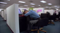 Medium shot male office worker sleeping with head on desk in cubicle / Los Angeles, California