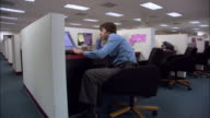 Medium shot male office worker slouching at desk, tapping on keyboard and yawning in cubicle / Los Angeles