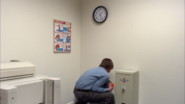 Medium shot male office worker struggling to put jug on water cooler/ tie getting caught in water cooler/ low angle