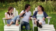 Medium shot man and two women hanging out on lawn in adirondack chairs/ Roxbury, New York