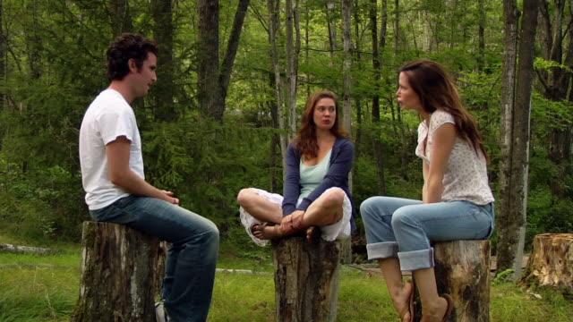 Medium shot man and two women sitting on stumps in woods/ Roxbury, New York