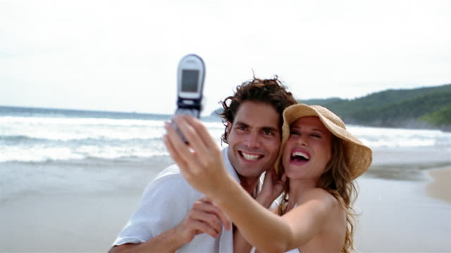 Medium shot man and woman taking pictures with camera phone on beach