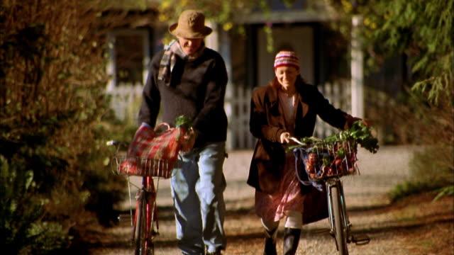 Medium shot man and woman walking with bicycles / Bainbridge Island, Washington