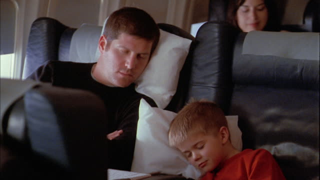 Medium shot man and young boy sleeping on airplane / flight attendant pulling blanket around boy