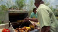 Medium shot man barbecuing at grill and woman pouring lemonade in yard / boy walking up to grill with plate