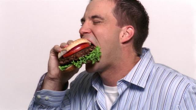 Medium shot man biting into hamburger