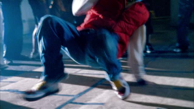 Medium shot man breakdancing in warehouse as people watch