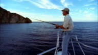 Medium shot man casting fishing line from bow of boat/ Long Beach, California