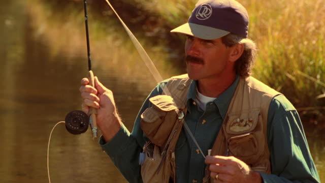 Medium shot man casting line while fly fishing / Arizona