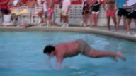 Medium shot man diving into pool during belly flop contest / Miami