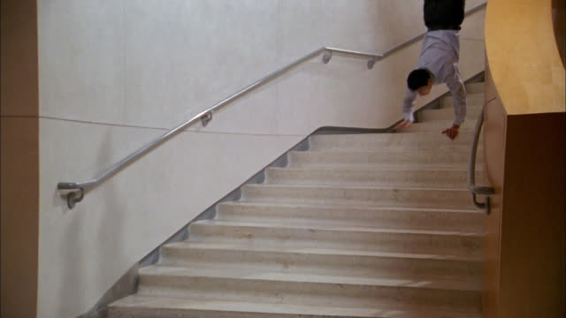 Medium shot man doing handstand walking down stairs and turning down hall