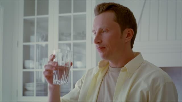 Medium shot man drinking water in kitchen/ Solebury, Pennsylvania