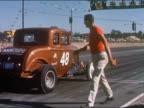 1959 medium shot man finished checking tire of bronze car  / race car taking off and speeding down track