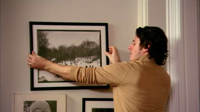 Medium shot man hanging picture in living room as woman advises/ Brooklyn, New York