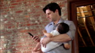 Medium shot man holding baby and talking on cell phone