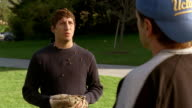 Medium shot man holding baseball mitt oblivious to bees crawling all over his head talking to friend in park