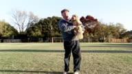 Medium shot man holding Lhasa Apso in park on autumn day
