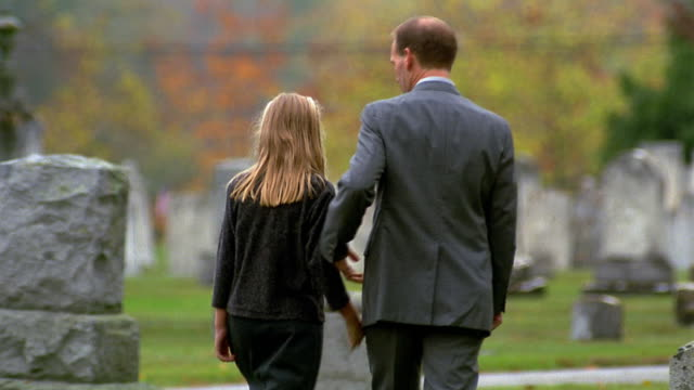 Medium shot man hugging girl as they walk in cemetery / Vermont