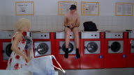 Medium shot man in boxer shorts sitting in laundromat as woman loads washing machine / Berlin, Germany