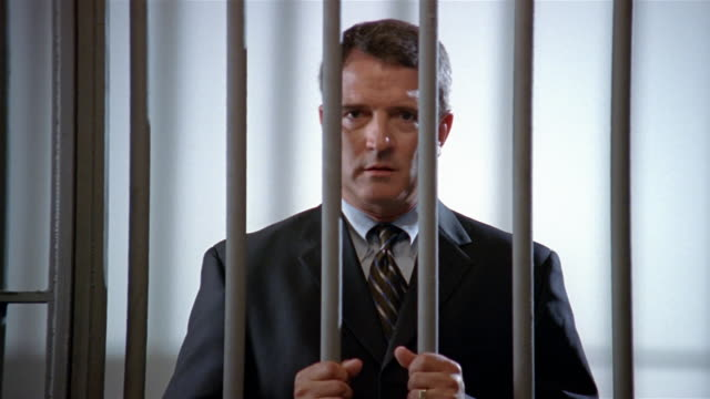 Medium shot man in suit in prison holding onto bars and looking at camera/ man looking down