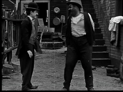 1918 B/W Medium shot man kicking other man/ men both dance around/ one man picking up bricks