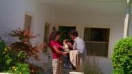 Medium shot man kissing woman holding baby goodbye and waving / California