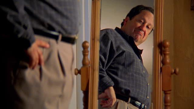 Medium shot man looking at himself in mirror happily