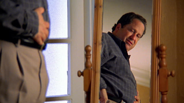 Medium shot man looking at himself in mirror unhappily