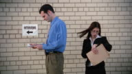 Medium shot man looking at paper and woman looking around in line for job interview