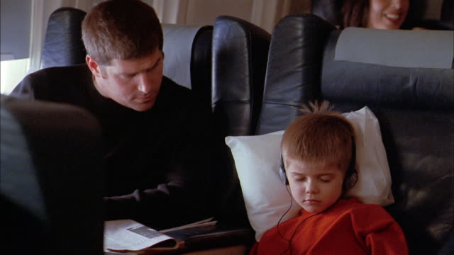 Medium shot man looking out airplane window / man taking headphones off sleeping boy and adjusting blanket
