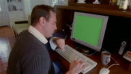 Medium shot man making online purchase on PC with green screen on monitor/ Solebury, Pennsylvania