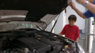 Medium shot man opening hood of car / father and son looking at engine