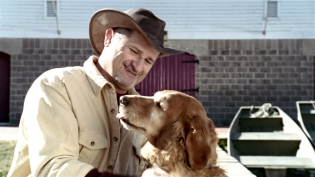 Medium shot man petting golden retriever and smiling at camera